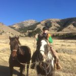 Boy Riding Paint Horse and Leading a Brown Horse - Yellowstone Horseback Riding